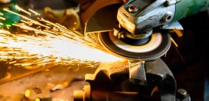 Angle grinder cutting scrap metal with sparks