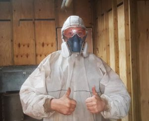 Man wearing goggles and face mask with thumbs up